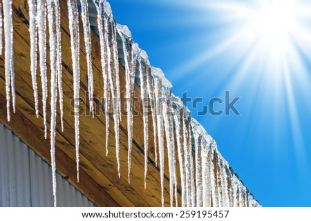 Long icicles against the solar sky. Spring comes. - stock photo