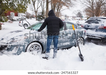 LONG ISLAND, NEW YORK - JANUARY 27,  2015:  Young man digging out and removing snow from cars after blizzard that hit the North East on Jan. 26 and 27, 2015. - stock photo