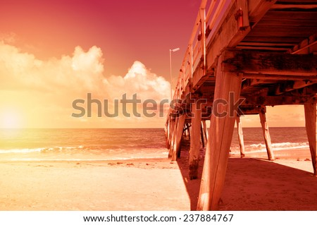Long jetty pier on wide open sandy beach overlooking ocean. Sunset. Taken at Henley Beach, South Australia.  - stock photo