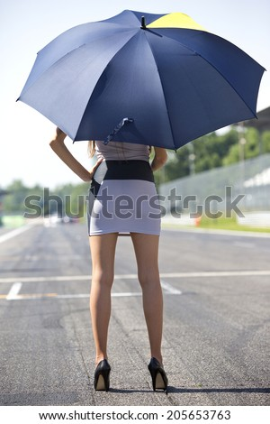 Long legged grid girl standing on the grid of a circuit, holding an umbrella - stock photo