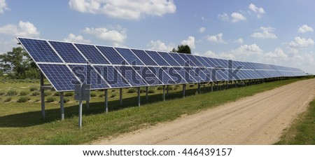Long line of no name solar electric generation panels is near the rural road. Panoramic collage from several photos - stock photo