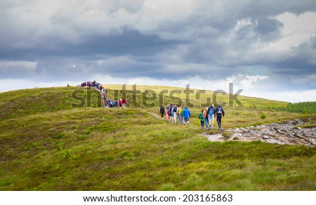 Long line of tourists in the Wicklow Mountains - stock photo