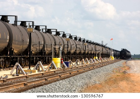 Long lines of railroad oil tanker cars stretch off into the distance down the train tracks waiting to be unloaded. - stock photo