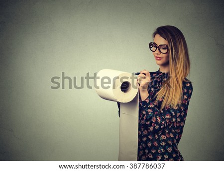 Long list of things to do. Young woman writing down ideas isolated on gray wall background. Attractive girl planning. Human face expression  - stock photo