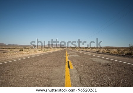 long lonely old asphalt road Route 66 and blue sky, lange einsame alte Route 66 mit blauen Himmel - stock photo