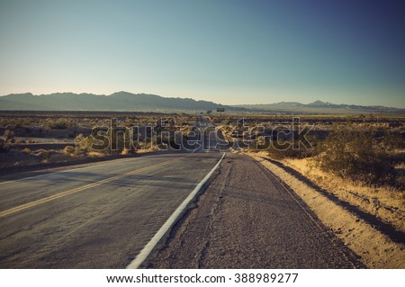 long old asphalt road Route 66 through desert and blue sky - stock photo