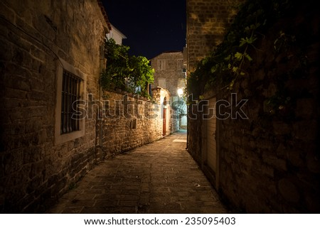 Long old narrow street lit by gas lanterns at night - stock photo