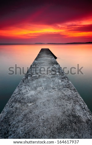 Long Path Of Jetty During Sunset - stock photo