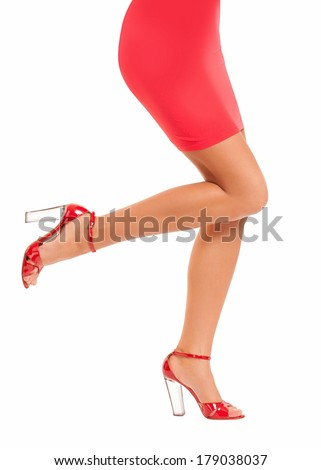 Long perfect female legs wearing high heels red shoes isolated on white background - stock photo