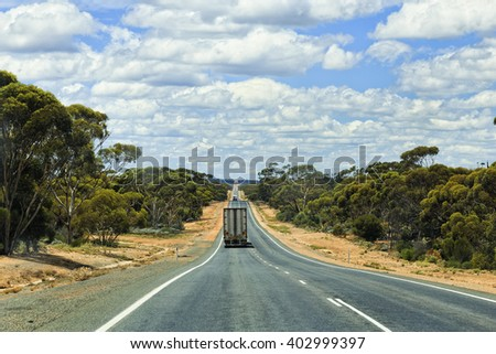 Long remote eyre highway in Nullarbor plain of Western Australia with lonely road train truck and tourist caravan van between eucalyptus woods. - stock photo