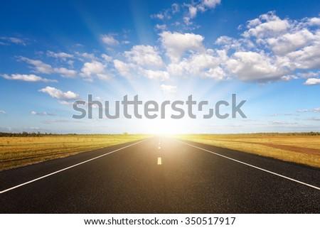 Long road at sunset  - stock photo