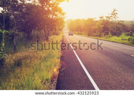 Long road at sunset with blur cars;vintage filter