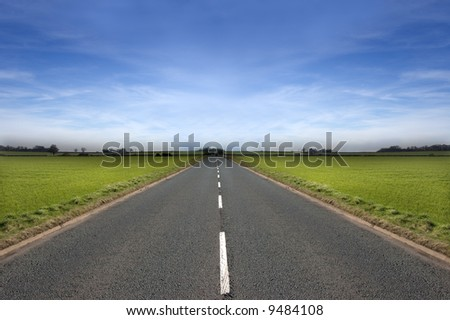 Long road stretching out into the distance under a dramatic blue sky - stock photo