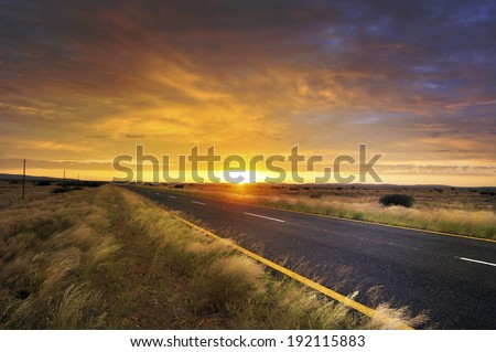 Long road through African savannah and beautiful sunrise - stock photo