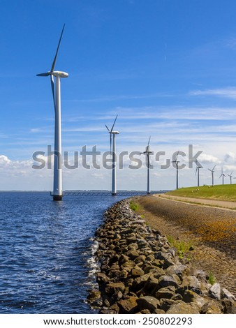 Long Row of wind turbines in the sea along a dike in the Netherlands - stock photo