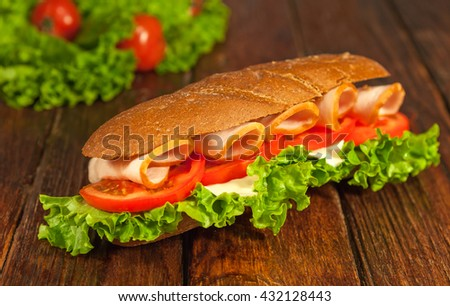 Long sandwich with lettuce, slices of fresh tomatoes, ham, and cheese on a brown wooden table. - stock photo
