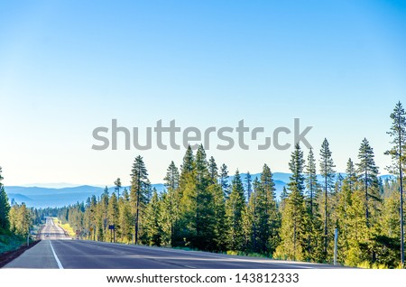 Long scenic highway passing through a lush green forest with blue hills in the background near Bend, Oregon - stock photo