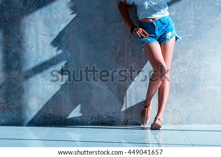 long sexy legs of beautiful women jeans shorts fashion sunny day standing near to the wall, hipster style - stock photo