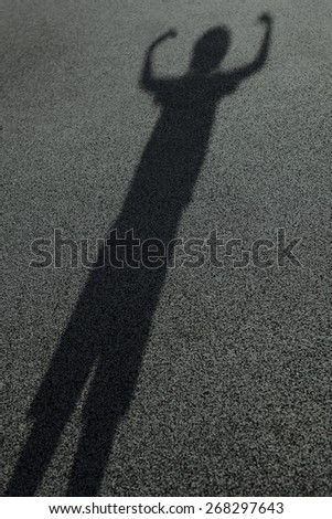 Long shadow of a kid raising hands in the street, high contrast, black and white artistic abstract photo with selective focus  - stock photo