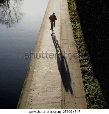 Long shadow of bicyclist on a sunny afternoon - stock photo