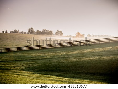 Long Shadows of Horse Fences in the Fog as the sun rises over the hills - stock photo