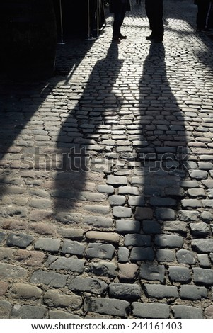 Long shadows of people standing on the cobble street - stock photo
