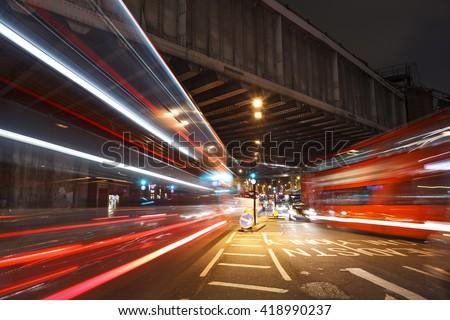 Long shutter near to the London Bridge Station. Busy traffic under the railway bridge at night. - stock photo