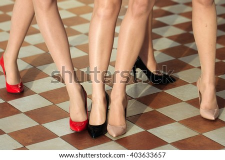 Long slim beautiful female feet in footwear - stock photo