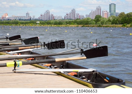 Long sport boat with oars stands at wooden pier at background of urban landscape. Focus on oars. - stock photo