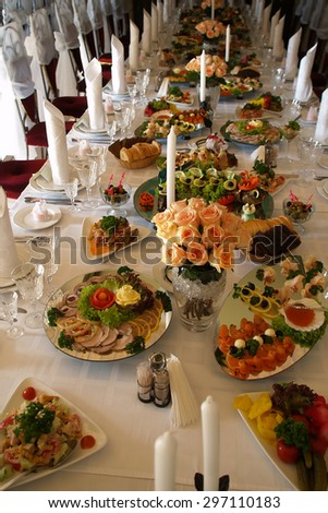 Long spread served festively decorated table with rose bouquets fabric napkins white candles and different snacks with nobody, vertical picture - stock photo