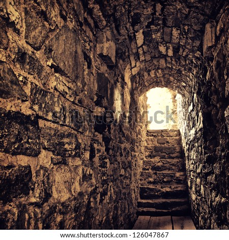 long stone corridor with stairway in ancient castle - stock photo