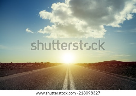 Long straight road at sunset  - stock photo