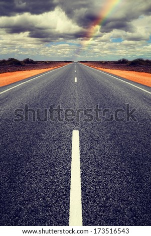 Long straight road in Western Australia with gathering storm clouds overhead. Concepts of trouble ahead and finding a way through. Road is symmetrical has been mirrored. - stock photo