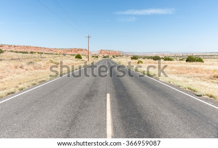 Long straight road Route 66  ahead paralleling the current interstate highway to left through desert of New Mexico, USA. - stock photo