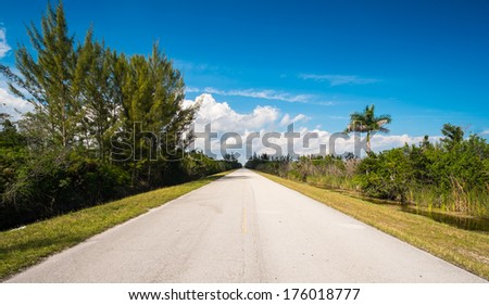 Long straight two lane rural road along a canal. - stock photo