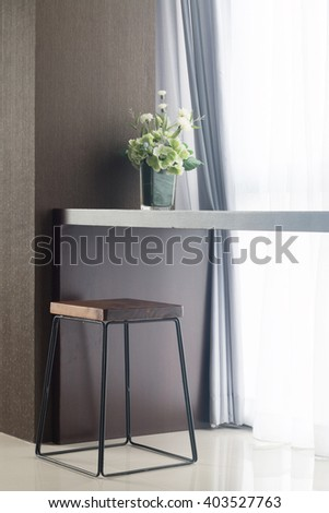 long table near window with vase and chair. - stock photo