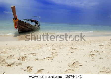 long-tail boat on the beach - stock photo