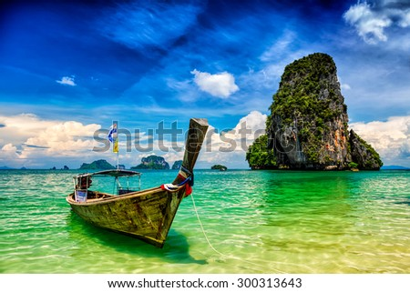Long tail boat on tropical beach (Pranang beach) and rock, Krabi, Thailand - stock photo