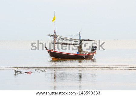 Long-tailed boat cast anchor on the beach at fishing village village, small island, Thailand. - stock photo