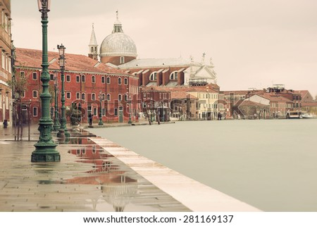 long time exposure of Chiesa del Santissimo Redentore (Church of the Most Holy Redeemer) and shoreline in Venice (Venezia) on a rainy day in autumn, Italy, Europe, vintage filtered style - stock photo
