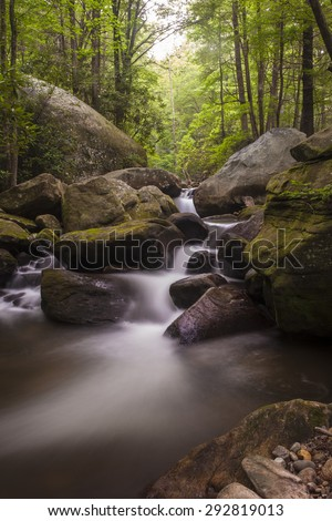 Long time exposure of water cascading over rocks in lush forest - stock photo