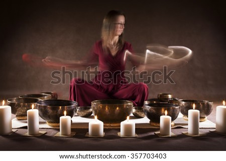 Long time exposure photo of a woman playing a Tibetan bowls, focus on a singing bowls - stock photo