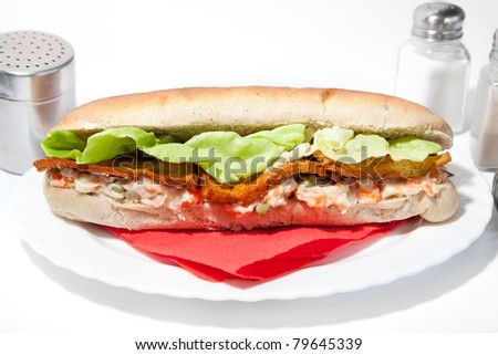 Long vegan sandwich made from integral bred with tofu fry cheese, russian salad with soya mayonnaise and  lettuce leaves serve on plate - stock photo