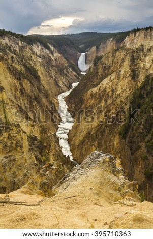 Long view of lower falls of the Yellowstone River with pines on the shore and steep yellow cliffs, Wyoming.. - stock photo