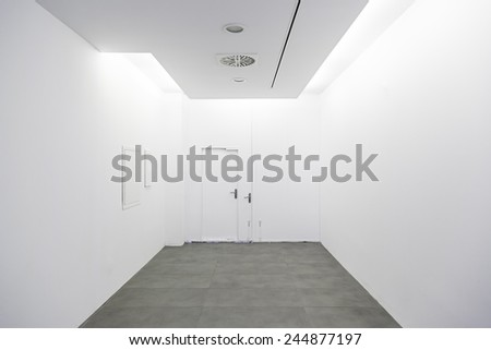Long walkway and white wall, detail of a hospital corridor - stock photo