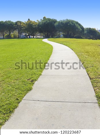 Long, winding road. Peaceful, empty, and winding paved pathway cuts through a green grassy field in a suburban park. - stock photo