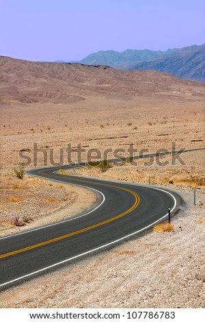 Long winding road through the hot deserts of Death Valley in California - stock photo