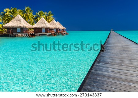 Long wodden jetty extended into azure water of lagoon with villas over the water - stock photo