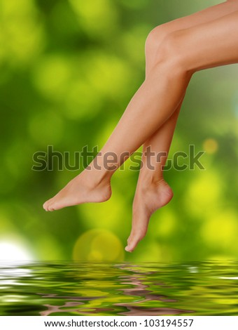 Long woman legs  on green background. Spa concept - stock photo