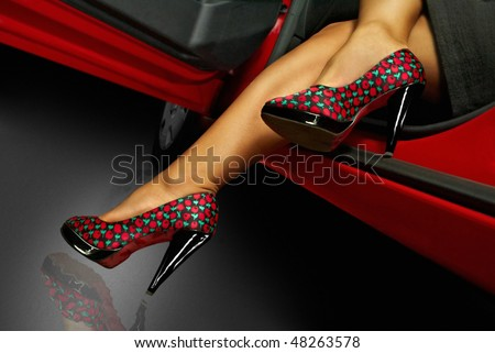 Long woman's legs in the shoes with red car - stock photo